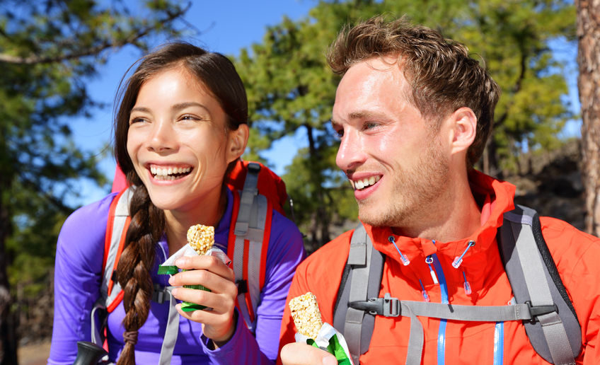 32707644 - couple eating muesli bar hiking. happy people enjoying granola cereal bars living healthy active lifestyle in mountain nature. woman and man hiker sitting laughing during hike.