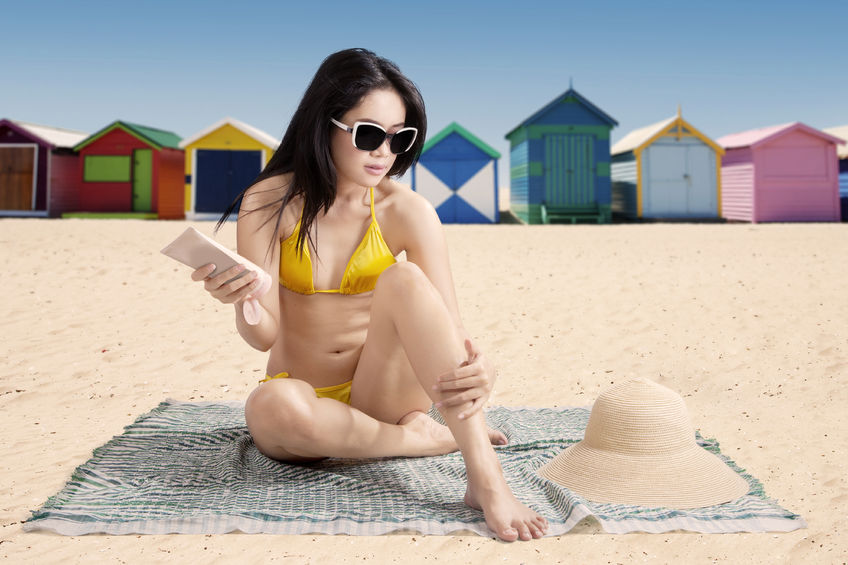 38982656 - young asian lady wearing swimsuit while sitting at beach and using suntan lotion with the background of the beach cottage