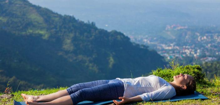 woman relaxes in yoga asana savasana