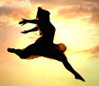 silhouette of a woman leaping through the air in front of a pink sunset
