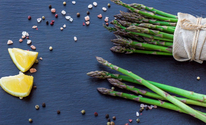 57106915 - healthy concept. bunch of organic fresh asparagus with ingredients for cooking on a grunge stone table. selective focus