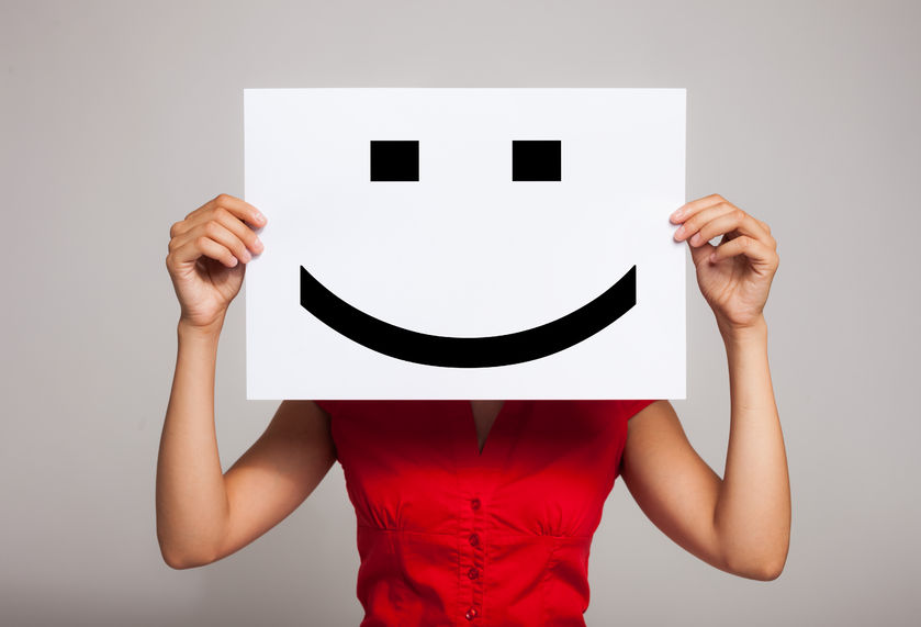 24322300 - woman holding a smiling face emoticon