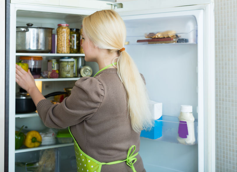 36833041 - blonde american woman looking for something in fridge at home kitchen