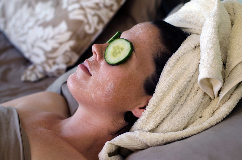45762794 - a young caucasian woman relaxes at home in bed with a natural eye and face treatment.