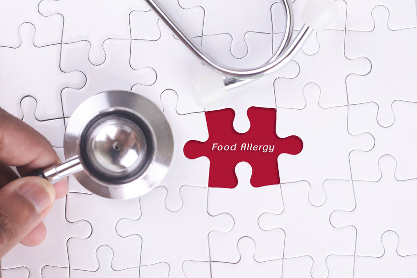 58482989 - medical concept - a doctor holding a stethoscope on missing puzzle with food allergy word