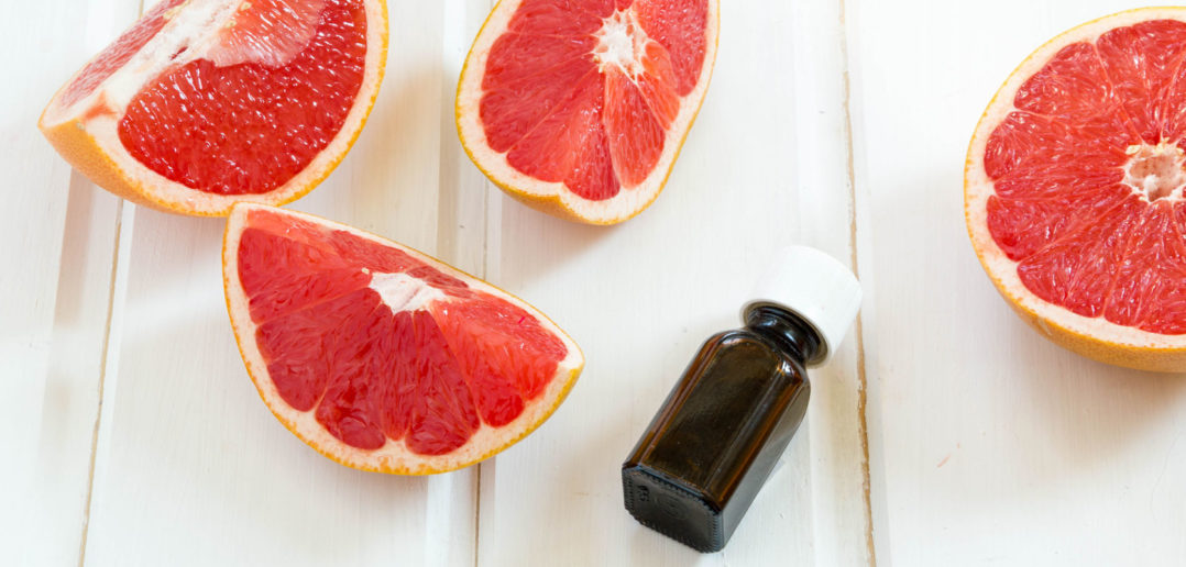 52122731 - essential oil in glass bottle with fresh, juicy grapefruit. spa concept. selective focus.