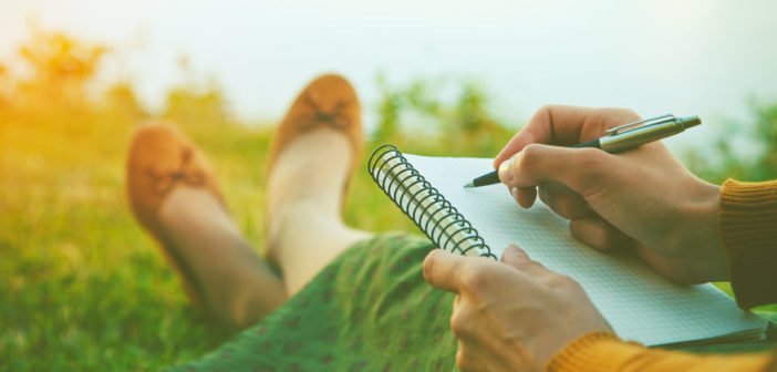46650488 - female hands with pen writing on notebook on grass outside