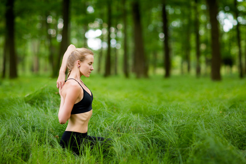 61636162 - nature yoga session in beautiful green polish woods, between trees. gomukhasana, cow face pose. heatlhy lifestyle concept.