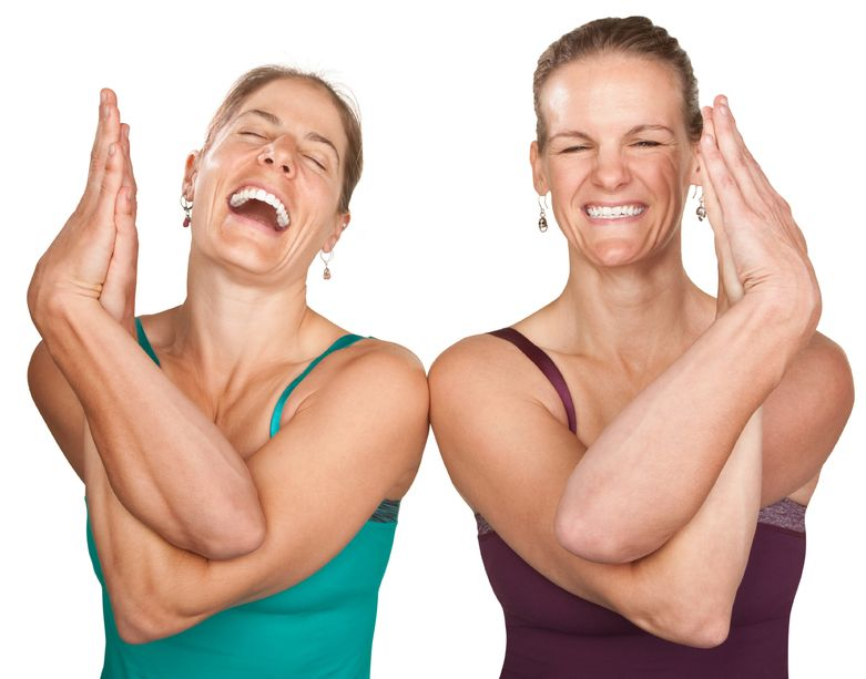 12638250 - two laughing women performing entwined namaskar over white background