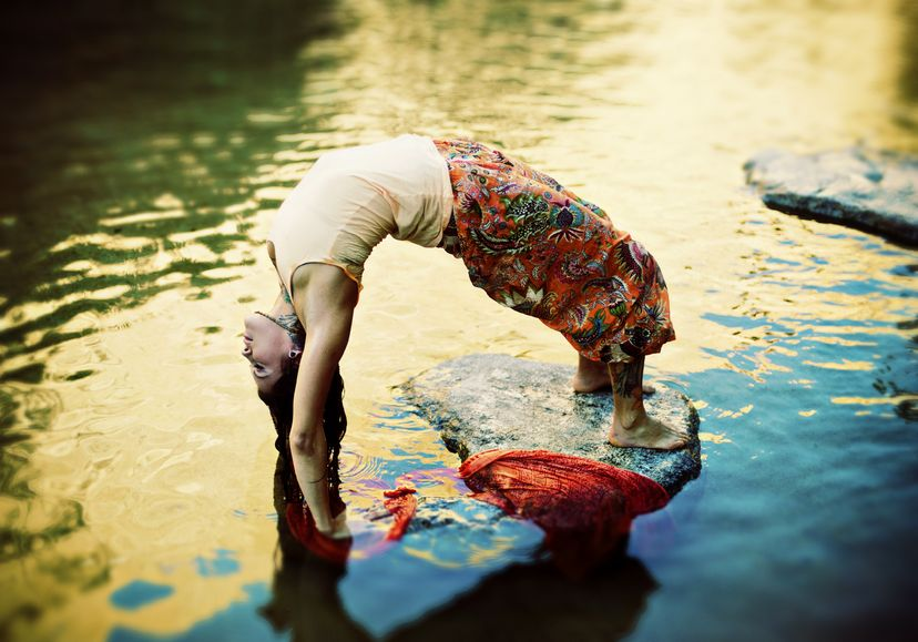 17162467 - yoga woman outdoors in yoga pose urdhva dhanurasana in a colorful pond